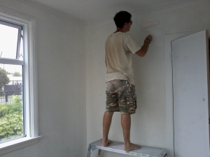 The Renovator touches up the undercoat around the new wardrobe door.